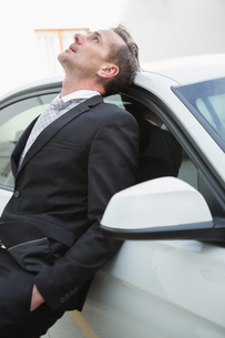 Upset businessman leaning on his carの写真素材 [FYI00005412]