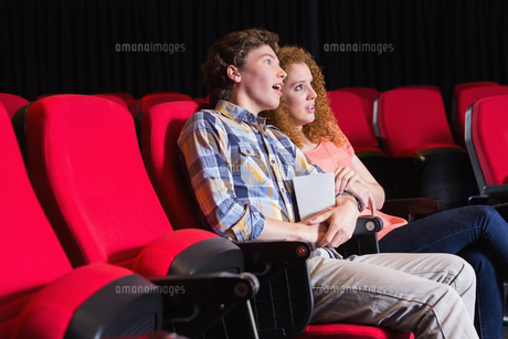 Astonished young couple watching a filmの写真素材 [FYI00005422]