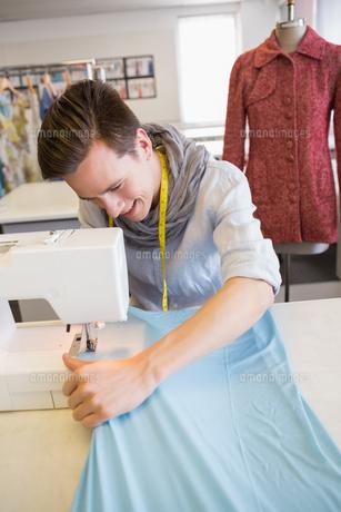 Smiling student using sewing machineの写真素材 [FYI00005451]