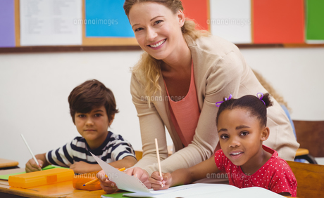 Pretty teacher helping pupil in classroomの写真素材 [FYI00005457]