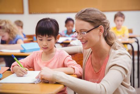 Pretty teacher helping pupil in classroomの写真素材 [FYI00005459]