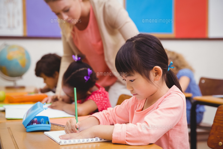 Cute pupils writing at desk in classroomの写真素材 [FYI00005464]