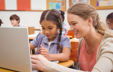 Cute pupil using computer with teacherの写真素材 [FYI00005469]