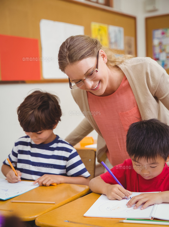 Pretty teacher helping pupil in classroomの写真素材 [FYI00005486]