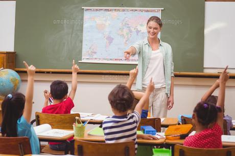 Pupils raising hand in classroomの写真素材 [FYI00005498]