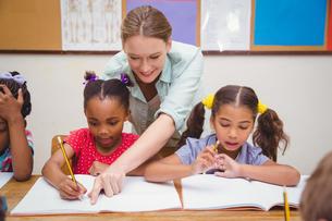Pretty teacher helping pupil in classroomの写真素材 [FYI00005505]