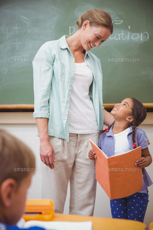 Cute pupil smiling to her teacher during class presentationの写真素材 [FYI00005509]