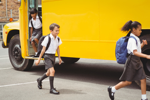 Cute schoolchildren getting off the school busの写真素材 [FYI00005511]