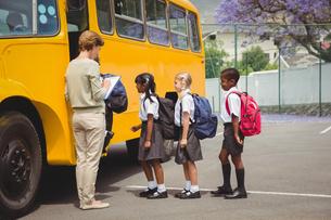 Cute schoolchildren waiting to get on school busの写真素材 [FYI00005523]