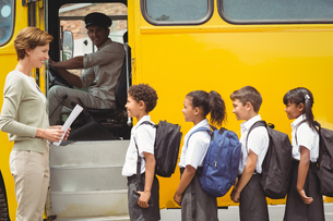Cute schoolchildren waiting to get on school busの写真素材 [FYI00005525]