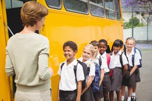 Cute schoolchildren waiting to get on school busの写真素材 [FYI00005526]