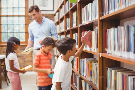 Cute pupils and teacher looking for books in libraryの写真素材 [FYI00005527]