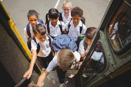 Cute schoolchildren getting on school busの写真素材 [FYI00005531]