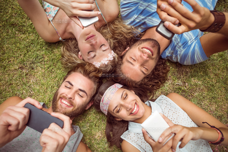 Hipsters lying on grass using smartphonesの写真素材 [FYI00005604]