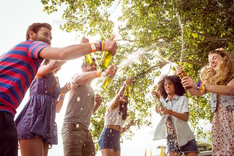 Happy hipsters spraying beer bottlesの写真素材 [FYI00005656]