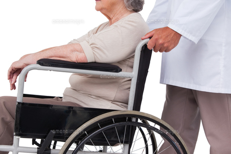 Doctor pushing patient in wheelchairの素材 [FYI00005673]
