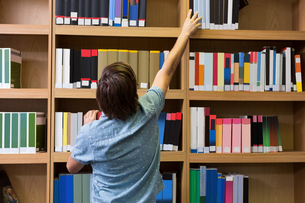 Student picking a book from shelf in libraryの素材 [FYI00005702]