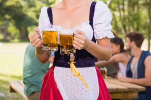 Pretty oktoberfest girl holding beer tankardsの写真素材 [FYI00005716]