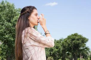 Pretty brunette using her inhalerの写真素材 [FYI00005745]