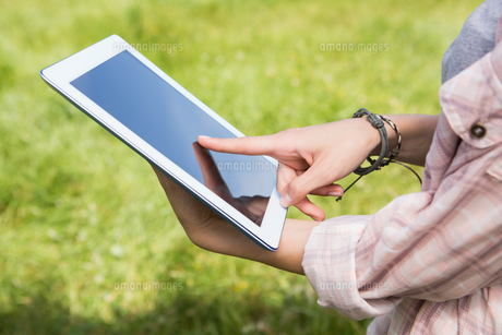 Woman using a tablet in the parkの素材 [FYI00005748]
