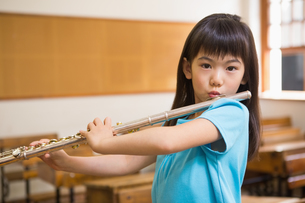 Cute pupil playing flute in classroomの写真素材 [FYI00005763]