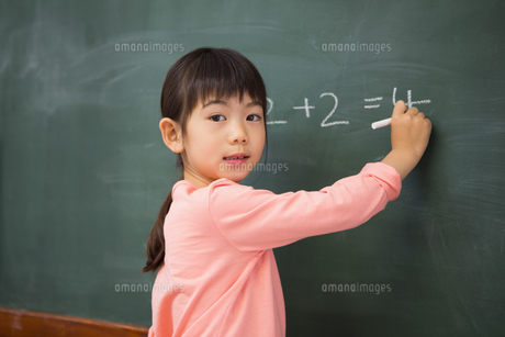 Pupil writing numbers on a blackboardの写真素材 [FYI00005764]