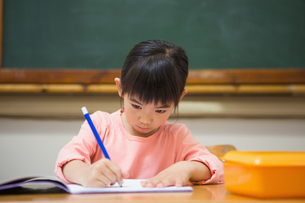 Cute pupil writing at desk in classroomの写真素材 [FYI00005766]