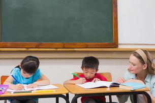 Cute pupils getting help from teacher in classroomの写真素材 [FYI00005771]