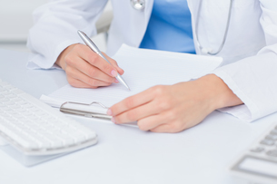 Female doctor writing prescriptions at tableの写真素材 [FYI00005781]