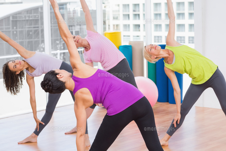 Female instructor guiding friends in stretching exerciseの素材 [FYI00005783]