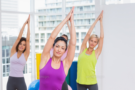 Women practicing stretching exercise in gymの写真素材 [FYI00005788]