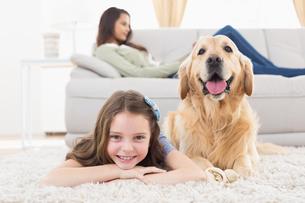 Girl with dog lying on rug at homeの写真素材 [FYI00005867]