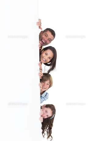 Happy family hiding behind billboardの素材 [FYI00005875]