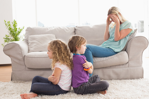 Angry siblings sitting arms crossed with upset mother on sofaの写真素材 [FYI00005907]