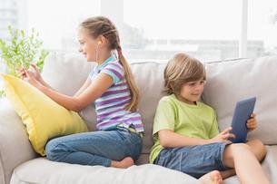 Siblings using technologies on sofaの写真素材 [FYI00005909]