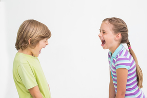 Siblings laughing on white backgroundの写真素材 [FYI00005913]