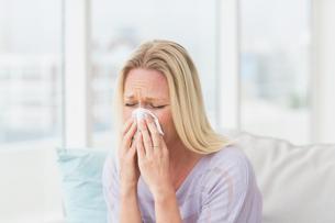 Woman sneezing in tissueの写真素材 [FYI00005916]
