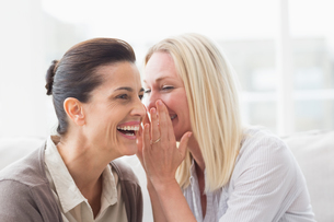 Woman revealing secret to her friend smilingの写真素材 [FYI00005917]