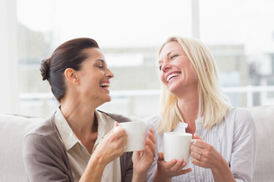 Women gossiping while having coffee in living roomの写真素材 [FYI00005921]