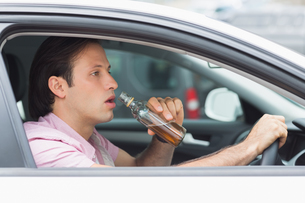 Man drinking alcohol while drivingの素材 [FYI00005923]