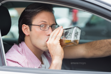 Man drinking alcohol while drivingの素材 [FYI00005926]