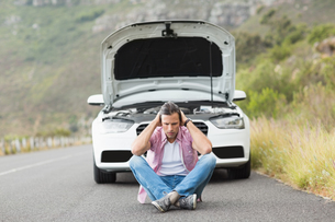 Stressed man sitting after a car breakdownの写真素材 [FYI00005927]