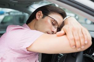 Drunk man slumped on steering wheelの写真素材 [FYI00005929]