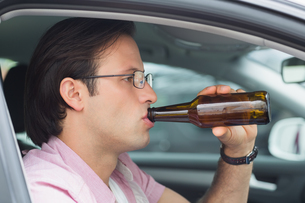 Man drinking beer while drivingの素材 [FYI00005930]