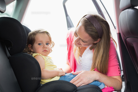 Mother securing her baby in the car seatの写真素材 [FYI00005964]