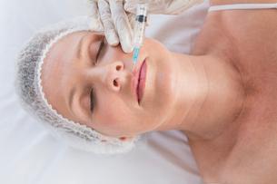 Woman receiving botox injection on her lipsの写真素材 [FYI00005969]