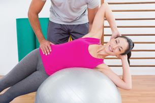 Trainer with smiling woman on exercise ballの写真素材 [FYI00005970]