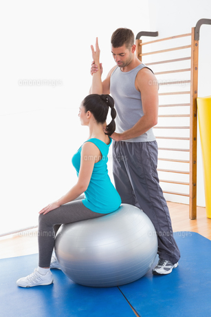 Trainer assisting woman exercising on fitness ballの写真素材 [FYI00005976]