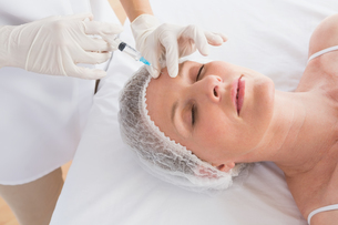 Woman receiving botox injection on her foreheadの写真素材 [FYI00005978]