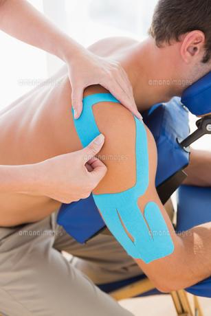 Doctor examining her patient shoulderの写真素材 [FYI00005981]